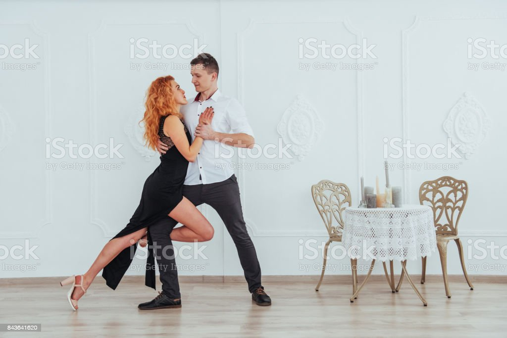 Young beautiful woman in a black dress and a man in white shirt dancing. stock photo