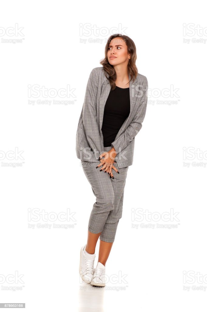 young beautiful woman in a jacket, blouse, sneakers and trousers need a toilet stock photo