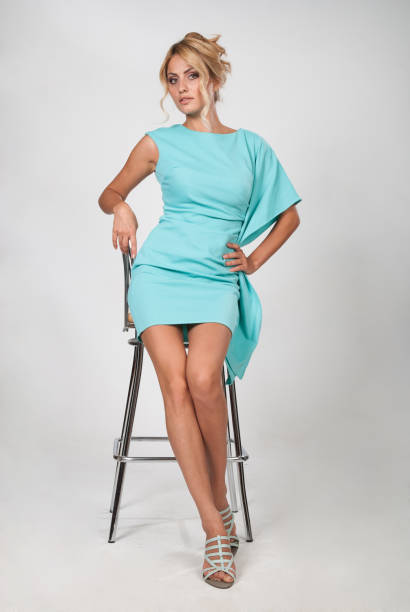 Young beautiful woman in a light blue dress sitting on a chair stock photo