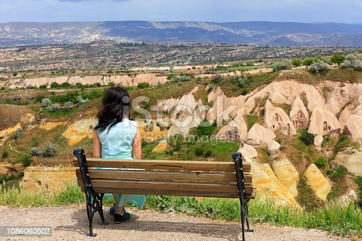 A young beautiful woman in a turquoise dress sits on a wooden bench on a hill and watches the panorama of the landscape of mountain caves and valleys in the canyons of Cappadocia