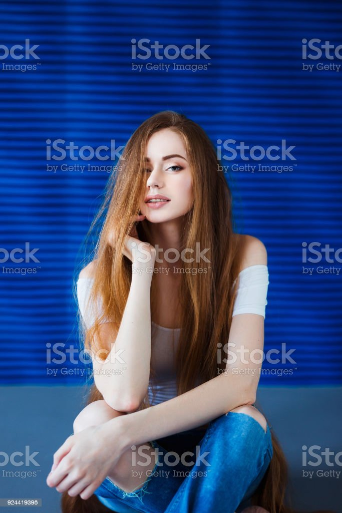 c33d0ee7d14 Young beautiful woman in a white shirt and jeans with very long natural hair  near a blue wall in loft interior - Stock image .