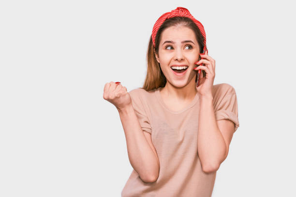 Young beautiful woman in beige t-shirt, red headband, smiling and talking on smart phone to her friend, looking cheerful and happy, posing on white studio background. Real human emotions. stock photo
