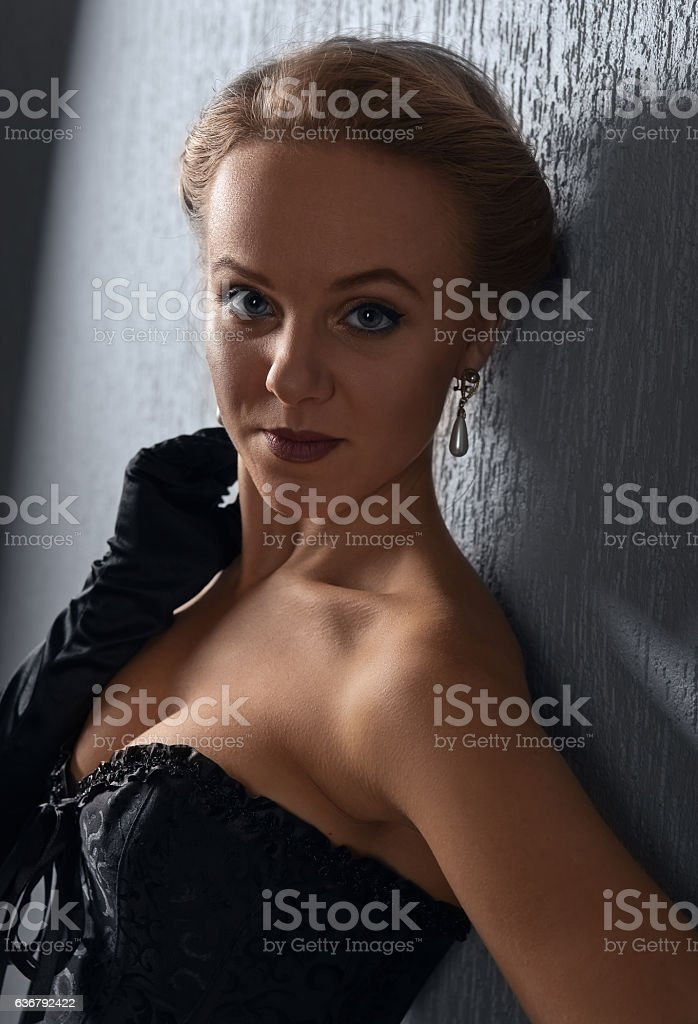 young beautiful woman in black corset with pearl earrings stock photo
