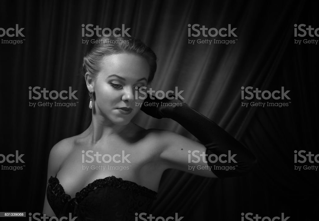Young beautiful woman in black with pearl earrings. stock photo