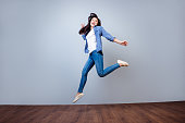 Young beautiful woman in checkered shirt jumping up against gray background