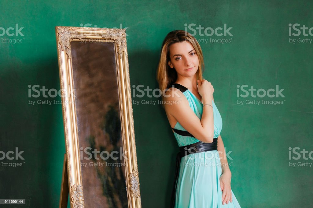 Young beautiful woman in cocktail dress standing near vintage mirror. With green empty wall on background, copyspace stock photo