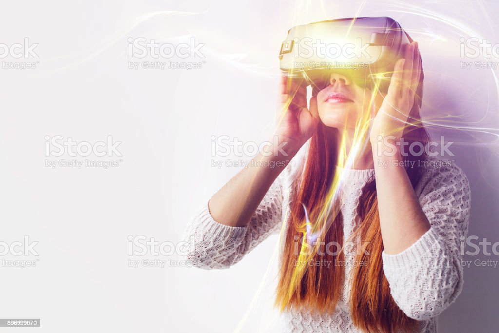 A young beautiful woman in glasses of virtual reality saw something amazing. Modern technologies. stock photo