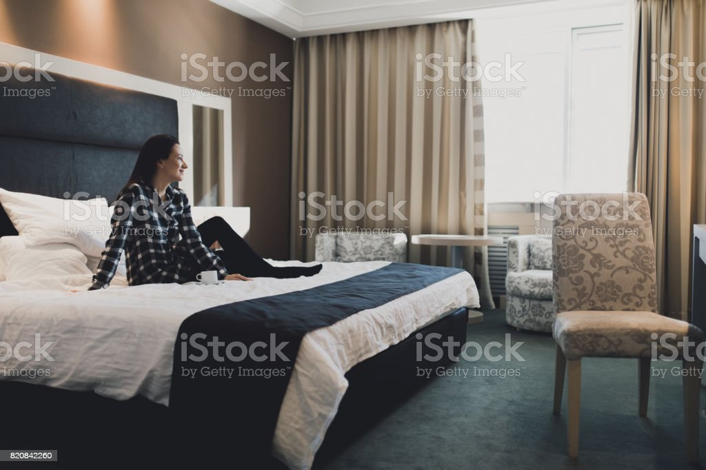 Young woman sitting in bed in hotel room with cup of coffee