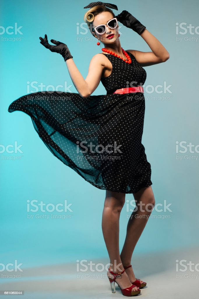 Young beautiful woman in retro pin-up style with fluttering dress stock photo
