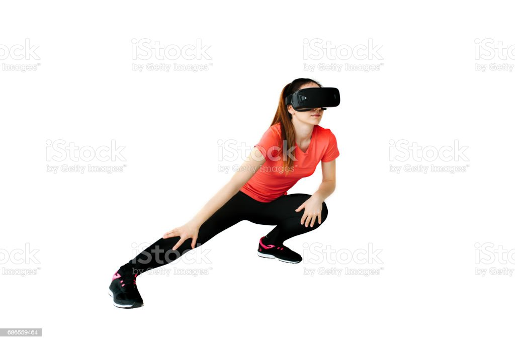 A young beautiful woman in virtual reality glasses makes aerobics remotely. Future technology concept. Modern imaging technology. Classes in single sports remotely. On a white background. foto stock royalty-free
