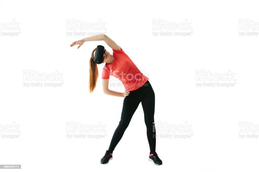 A young beautiful woman in virtual reality glasses makes aerobics remotely. Future technology concept. Modern imaging technology. Classes in single sports remotely. On a white background. royalty-free stock photo