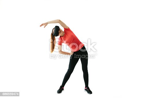 istock A young beautiful woman in virtual reality glasses makes aerobics remotely. Future technology concept. Modern imaging technology. Classes in single sports remotely. On a white background. 686559474