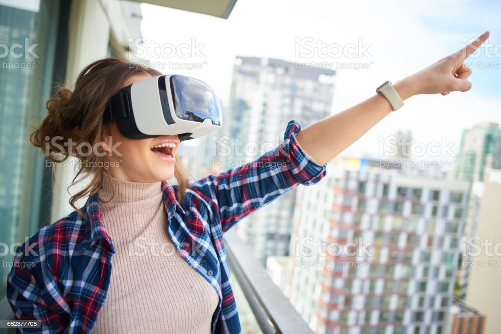 Young beautiful woman in virtual reality glasses on balcony royalty-free stock photo