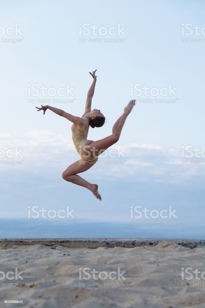 Young beautiful woman is dancing wearing body suit on sunrise in the desert stock photo