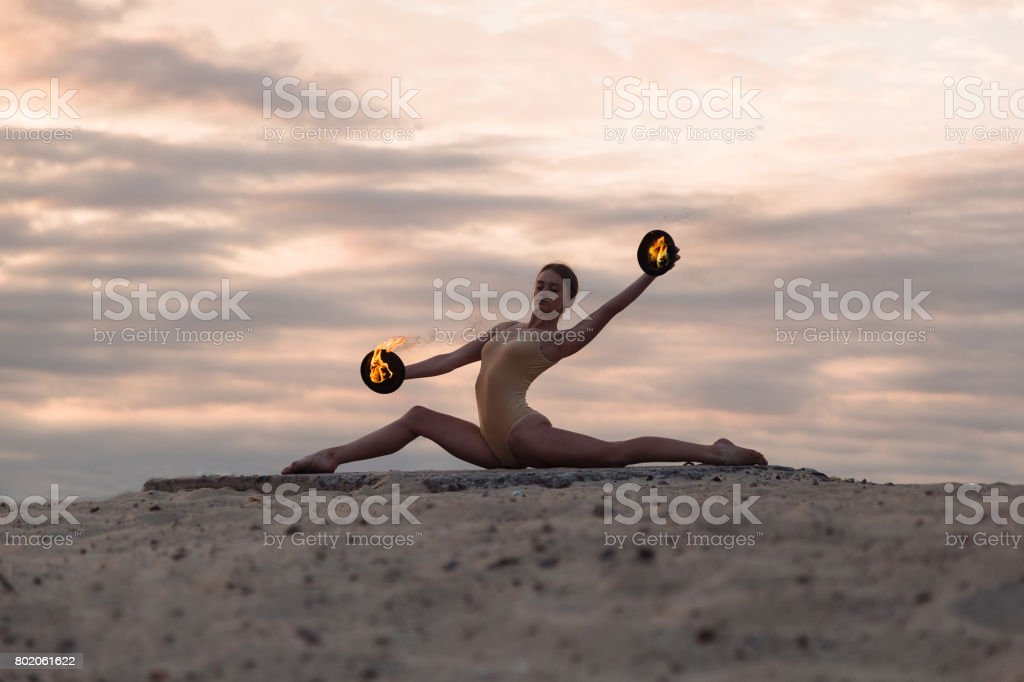 Young beautiful woman is dancing with fire wearing body suit on sunrise in the desert stock photo