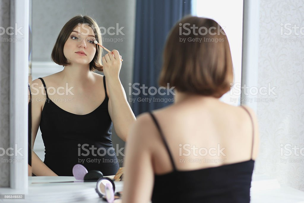 Young beautiful woman is doing makeup, looking in the mirror stock photo
