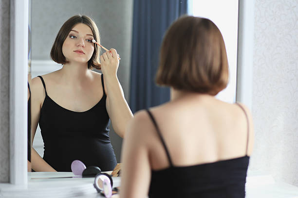 young beautiful woman is doing makeup, looking in the mirror - makeup for pregnant women stock photos and pictures