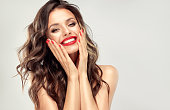 Young, beautiful woman is looking straight on viewer with wide, happy smile. Expression of gladness and sense of pleasure on the face of pretty model. Double colored, freely lieing hairstyle, bright sensual makeup with gilded eyelids and red lipstick. Human emotions.