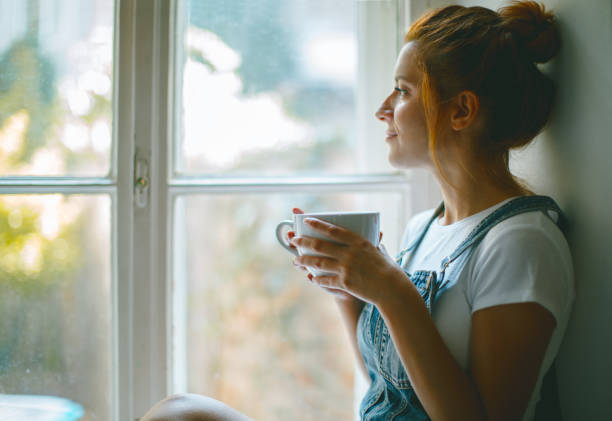 young beautiful woman is looking through the window and drinking coffee in the morning - looking at view stock pictures, royalty-free photos & images