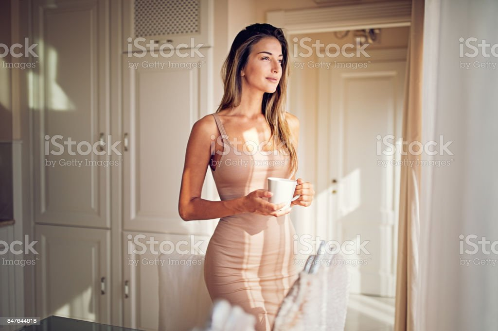 Young ,beautiful woman is looking through the window and drinking coffee in the morning stock photo