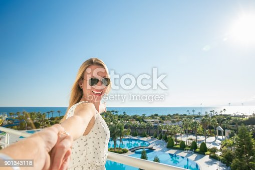 istock Young beautiful woman is looking to the sea 901343118