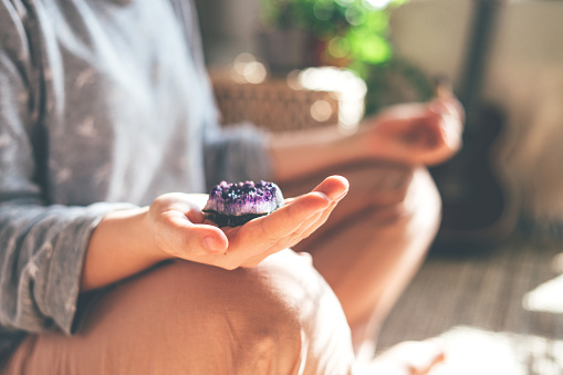 Young beautiful woman is meditating with a crystal quartz in her hand. Sits on the floor at home.