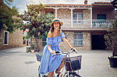 Young beautiful woman is riding bicycle in old sea village