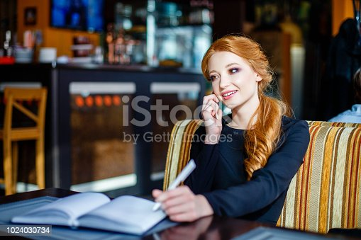 istock Young beautiful woman is talking on the phone and making notes in her notebook while sitting in a restaurant 1024030734