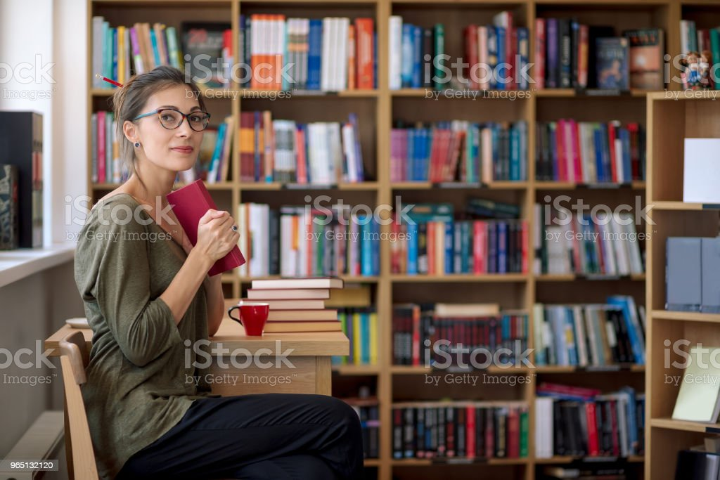 Young beautiful woman keep a book in her hand smiling zbiór zdjęć royalty-free