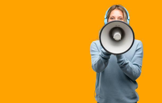 young beautiful woman listening to music communicates shouting loud holding a megaphone, expressing success and positive concept, idea for marketing or sales - talk in a radio foto e immagini stock