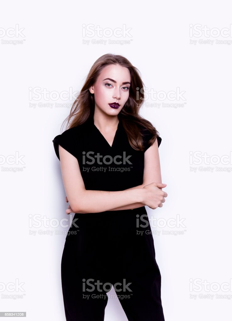 Young beautiful woman looks perfect wearing stylish black jumpsuit Dark luxury lipstick stock photo