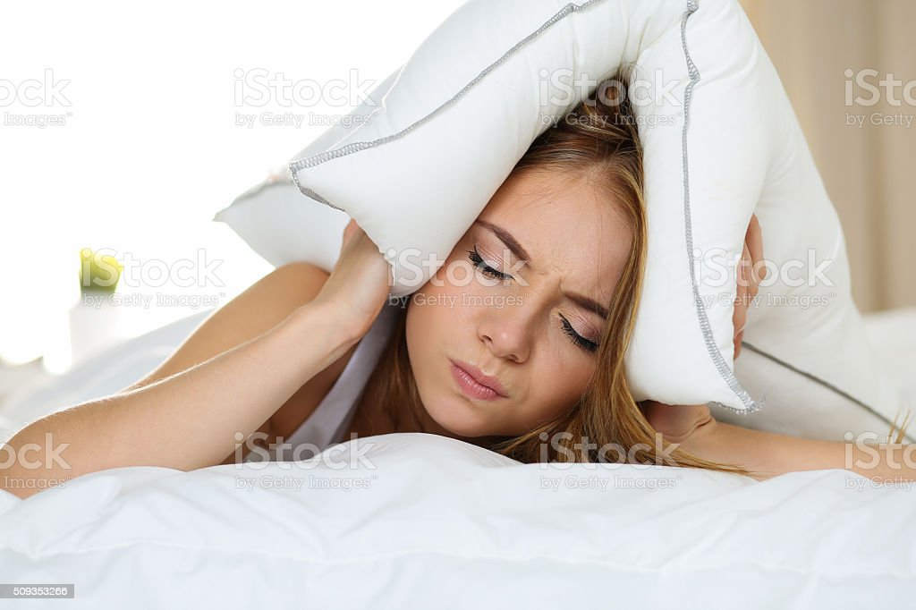 Young beautiful woman lying in bed suffering with insomnia stock photo