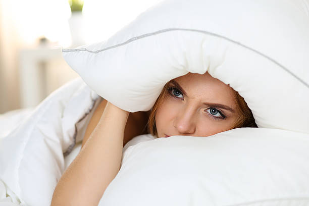 Young beautiful woman lying in bed suffering with insomnia Young beautiful woman lying in bed suffering with insomnia covering head and ears with pillow and making unpleasant face. Noisy neighbour, stress, alarm sound, prevent from sleep concept inconvenience stock pictures, royalty-free photos & images