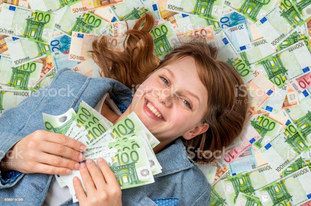Belle jeune femme se trouvant sur fond argent euro - Photo