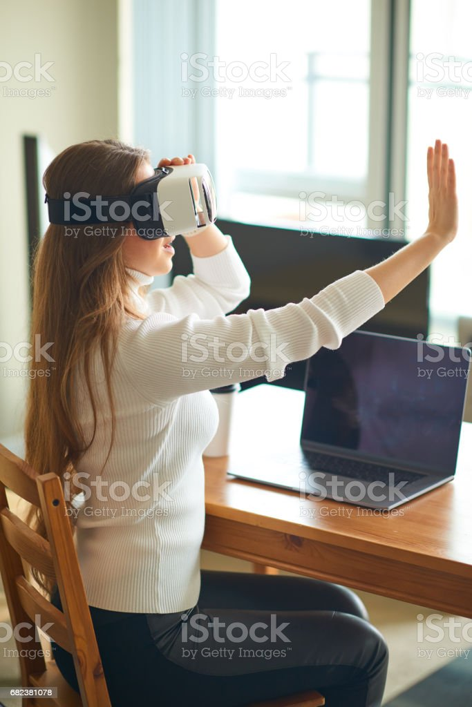 Young beautiful woman making a call while wearing virtual reality headset royalty-free stock photo