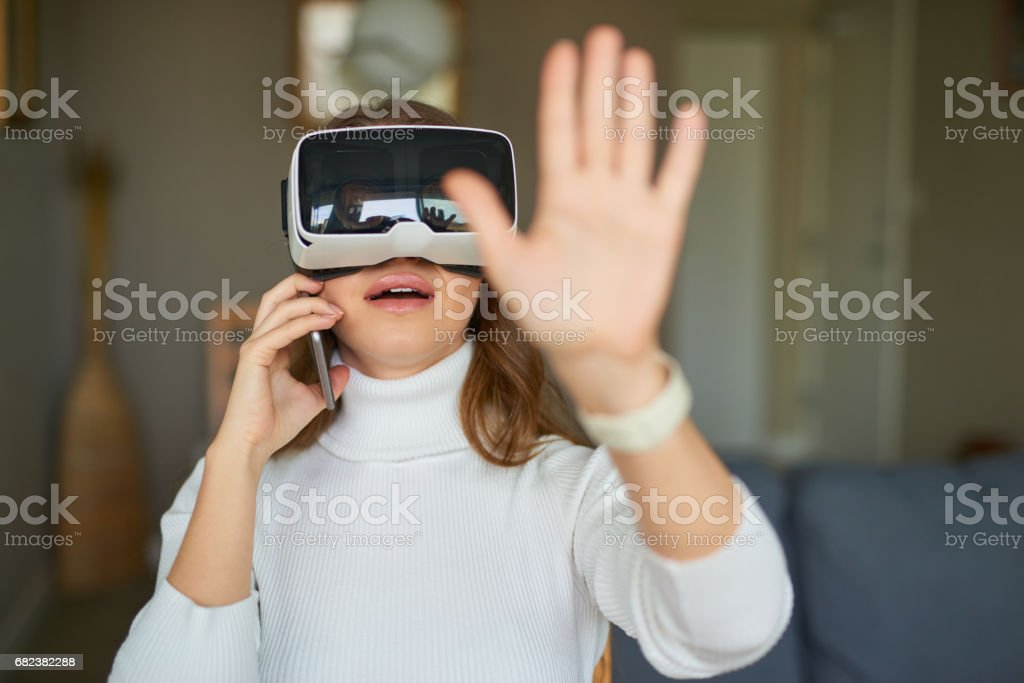 Young beautiful woman making a call while wearing virtual reality headset zbiór zdjęć royalty-free