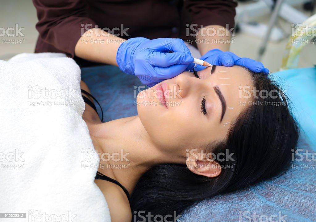 Young beautiful woman making permanent makeup in cosmetology salon. stock photo