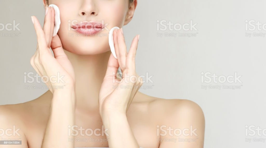 Young beautiful woman model is moisturing own face skin by cotton pads. Cosmetology. stock photo