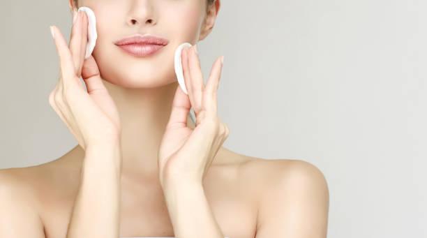 modèle de la belle jeune femme est hydratante au propre visage peau de tampons de coton. cosmétologie. - démaquillant photos et images de collection