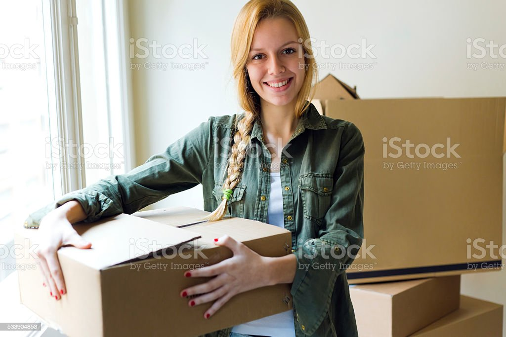 Young beautiful woman moving in a new home. stock photo