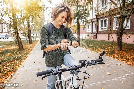 Young beautiful woman on a bicycle uses a smartwatch, navigation in the city