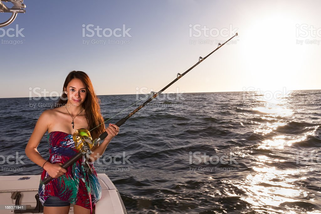 Young Beautiful Woman on a Boat with Fishing Rod royalty-free stock photo