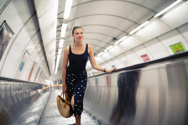 Junge schöne Frau auf einer Rolltreppe – Foto