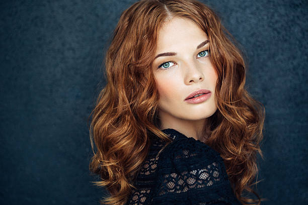 young beautiful woman on dark background - woman green eyes red hair stock photos and pictures