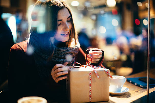 young beautiful woman opening a present. - birthday gift stock photos and pictures