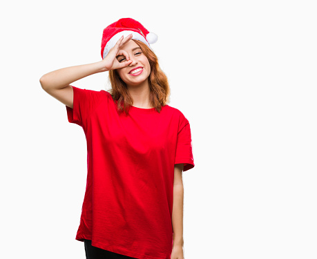 Young beautiful woman over isolated background wearing christmas hat doing ok gesture with hand smiling, eye looking through fingers with happy face.
