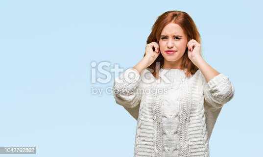 Young beautiful woman over isolated background wearing winter sweater covering ears with fingers with annoyed expression for the noise of loud music. Deaf concept.