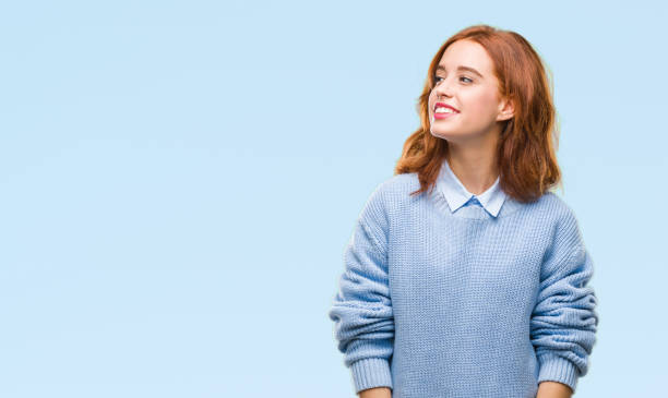 Young beautiful woman over isolated background wearing winter sweater looking away to side with smile on face, natural expression. Laughing confident. Young beautiful woman over isolated background wearing winter sweater looking away to side with smile on face, natural expression. Laughing confident. side view stock pictures, royalty-free photos & images