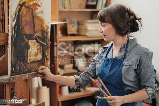 937313030 istock photo Young beautiful woman painter among easels and canvases in a bright studio. 1145251203