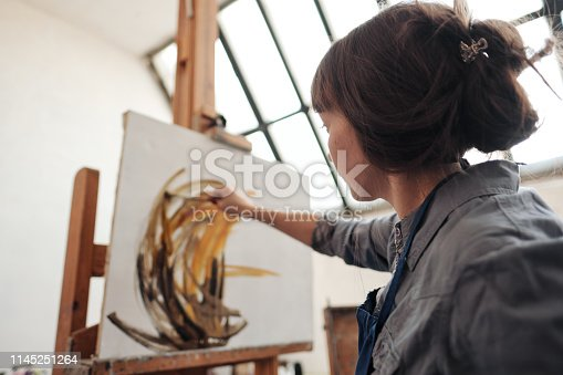 937313030 istock photo Young beautiful woman painter among easels and canvases in a bright studio. 1145251264